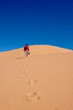 Укомплектуйте личным составом идти на песчанные дюны к небу Стоковое Изображение