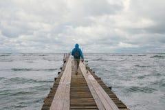 Укомплектуйте личным составом идти на пристань на предпосылке бурного моря Стоковая Фотография