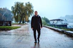 Укомплектуйте личным составом идти рекой на дождливый день Стоковое Фото