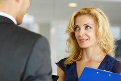 Укомплектуйте личным составом и усмехаясь женщина с голубой пусковой площадкой доски сзажимом для бумаги говоря в офисе Стоковые Фотографии RF