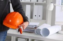 Укомплектуйте личным составом костюм архитектора нося держа шлем стоя в офисе Стоковые Фото