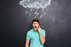 Укомплектуйте личным составом кричать на сотовом телефоне стоя с черной доской Стоковые Фотографии RF