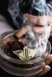 Укомплектуйте личным составом куря сигару и ashtray держать с банкнотой доллара Стоковые Фото
