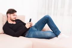 Укомплектуйте личным составом класть на софу держа smartphone и отправку СМС Стоковые Фото
