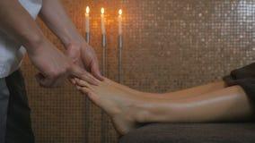 Укомплектуйте личным составом массажировать пальцы ` s девушки на левой ступне в курорте видеоматериал