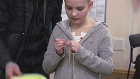 Укомплектуйте личным составом маленькую девочку порции с цветком на голове вязать вязанием крючком празднество творение handmade сток-видео