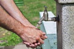 Укомплектуйте личным составом моя руку с водой от водопроводного крана в парке Стоковая Фотография RF