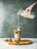 Укомплектуйте личным составом молоко руки ` s лить к замороженному коктеилю кофе карамельки latte Стоковые Изображения RF