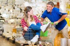 Укомплектуйте личным составом нажатие женщины в магазине оборудования ринва магазинной тележкаи стоковое фото rf