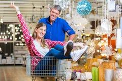 Укомплектуйте личным составом нажатие женщины в магазине оборудования ринва магазинной тележкаи стоковая фотография