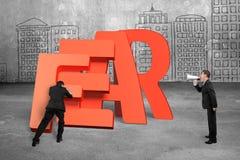 Укомплектуйте личным составом нажатие домино слова страха понижаясь с другим держа speake стоковое изображение
