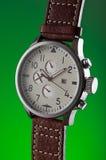 Укомплектуйте личным составом наручные часы металла ` s без логотипов на зеленой предпосылке Стоковые Фото
