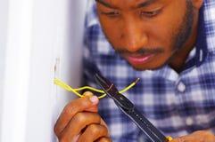 Укомплектуйте личным составом носить белую и голубую рубашку работая на электрических проводах стенной розетки используя отвертку Стоковые Изображения