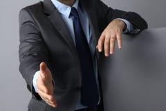 Укомплектуйте личным составом носить костюм предлагая трясти руки Стоковая Фотография