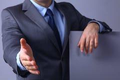 Укомплектуйте личным составом носить костюм предлагая трясти руки Стоковое Фото