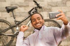 Укомплектуйте личным составом нося белую красную рубашку дела сидя вниз, задерживающ мобильный телефон принимая фото selfie, усме стоковая фотография