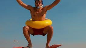 Укомплектуйте личным составом нося флипперы и резиновое кольцо на пляже видеоматериал
