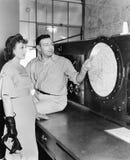 Укомплектуйте личным составом объяснять о радиолокаторе к молодой женщине в диспетчерском пункте (все показанные люди более длинн Стоковое Изображение