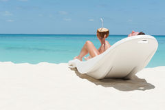Укомплектуйте личным составом ложь на sunbed lounger и выпейте коктеиль кокоса на wi пляжа Стоковые Изображения RF