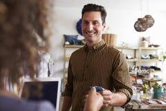 Укомплектуйте личным составом оплачивать продажи ассистентские с кредитной карточкой в магазине одежды стоковые фотографии rf