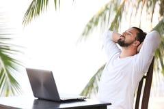 Укомплектуйте личным составом ослаблять на пляже с компьтер-книжкой, рабочим местом фрилансера, мечт работой Стоковые Фото