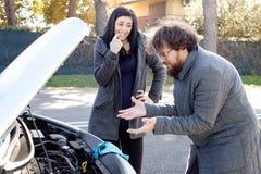 Укомплектуйте личным составом отчаянное о сломленном автомобиле пока подруга усмехается Стоковое Изображение RF
