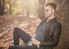 Укомплектуйте личным составом отдыхать около дерева в парке Стоковое Изображение