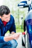 Укомплектуйте личным составом очищать эпицентр деятельности колеса сплава его автомобиля Стоковые Изображения