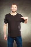 Укомплектуйте личным составом парня в пустой рубашке с указывать космоса экземпляра Стоковое Изображение RF
