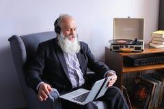 Укомплектуйте личным составом пенсионера восторженно и счастливо слушающ к песням fr стоковое фото