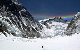 Укомплектуйте личным составом пеший поднимающий вверх Mt Эверест с радугой в небе Стоковые Фото