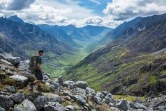 Укомплектуйте личным составом пеший туризм вниз с крутого следа в горах Talkeetna, Аляски Стоковые Изображения RF