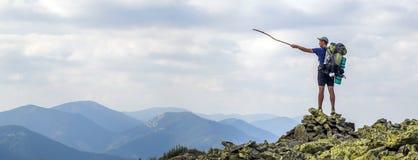 укомплектуйте личным составом пик горы Эмоциональное место Молодой человек с backpac Стоковые Фото