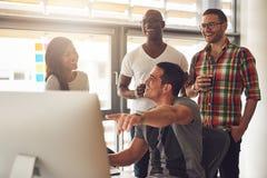 Укомплектуйте личным составом показывать что-то на компьютере к счастливым друзьям Стоковое Фото