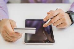 Укомплектуйте личным составом покупки используя ПК таблетки и кредитную карточку, крытые, конец-вверх Стоковые Изображения