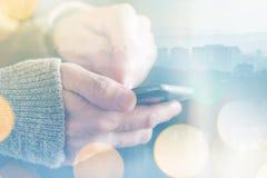 Укомплектуйте личным составом посылать текстовое сообщение на smartphone, солнечный свет утра до конца Стоковое фото RF