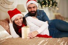 Укомплектуйте личным составом подарок присутствующего Нового Года девушки, пару рождества в кровати Стоковое Изображение RF