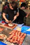 Укомплектуйте личным составом подготавливать кальмара быть проданным в рынке ночи города Kaohsiung Стоковая Фотография