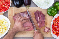 Укомплектуйте личным составом подготавливать мясо и овощи в кухне Стоковое Изображение