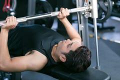 Укомплектуйте личным составом поднимаясь весы гантели пока лежащ вниз в спортзале Стоковое Фото