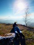 Укомплектуйте личным составом положение вниз и принимающ фото камерой зеркала на шеи Пик Snowy скалистый горы Стоковые Изображения RF