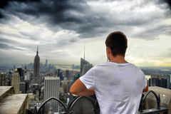 Укомплектуйте личным составом положение на верхней части крыши и смотреть на Нью-Йорке Стоковое Изображение