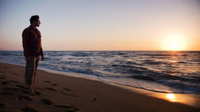Укомплектуйте личным составом положение на пляже и смотреть в заход солнца Стоковые Фотографии RF