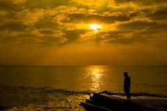 Укомплектуйте личным составом положение на пляже смотря яркое красное dur облаков шторма Стоковые Изображения