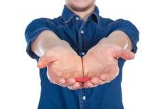 Укомплектуйте личным составом положение с красным сердцем в руках, изолированных на белой предпосылке стоковые фото