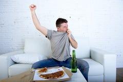 Укомплектуйте личным составом праздновать кресло цели дома смотря футбольную игру на телевидении Стоковое фото RF