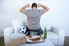 Укомплектуйте личным составом праздновать кресло цели дома смотря футбольную игру на телевидении Стоковые Фото
