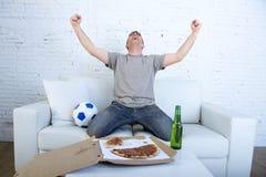 Укомплектуйте личным составом праздновать кресло цели дома смотря футбольную игру на телевидении Стоковое Фото