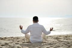 Укомплектуйте личным составом практикуя раздумье йоги на пляже на концепции образа жизни захода солнца здоровой Стоковое Фото