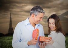 Укомплектуйте личным составом предлагая подарок к женщине с Эйфелевой башней в предпосылке стоковая фотография rf